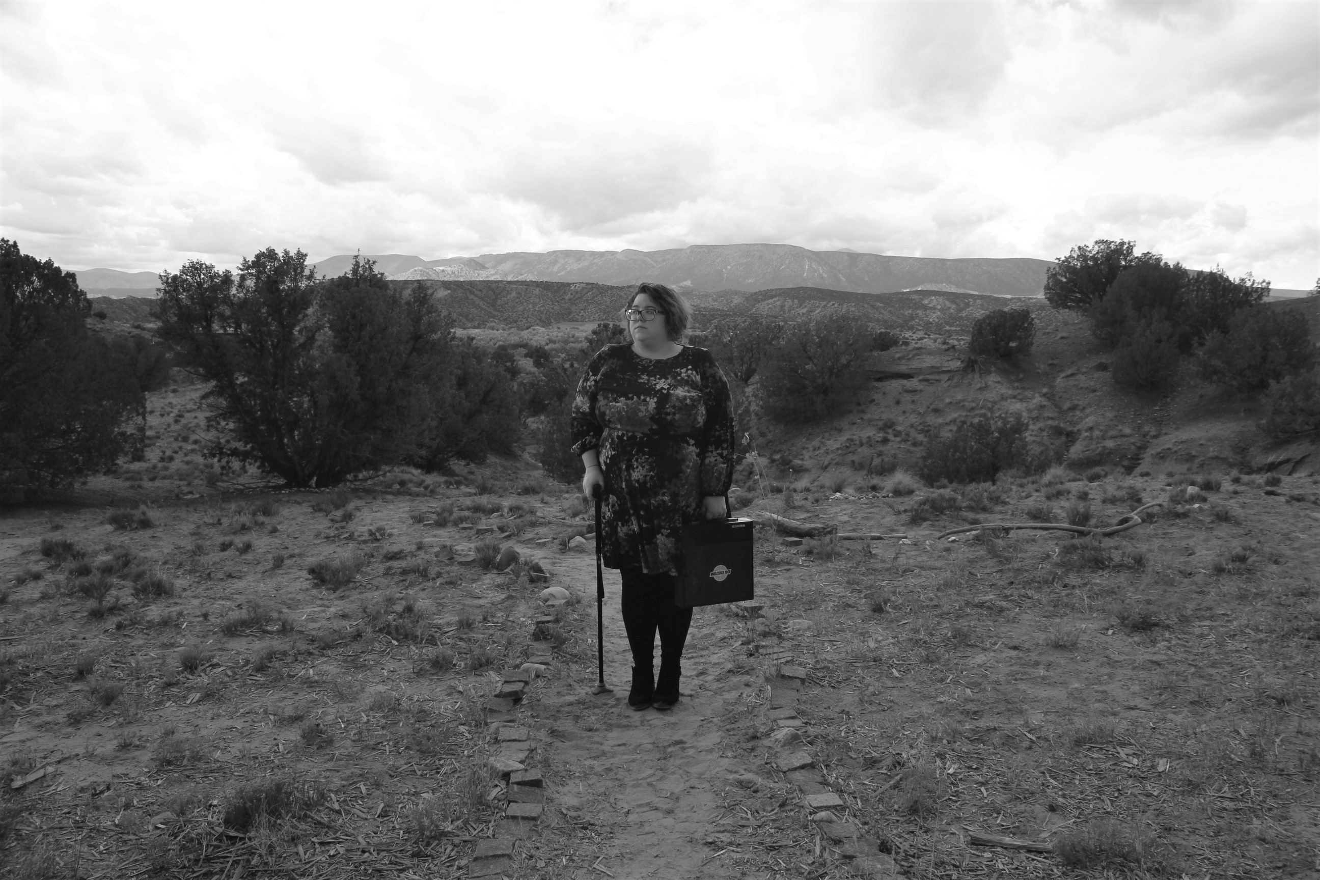 Alexandra stands with her black cane and a typewriter in the New Mexico desert with vistas behind her. The image is desaturated - not quite black and white, but mostly devoid of color.