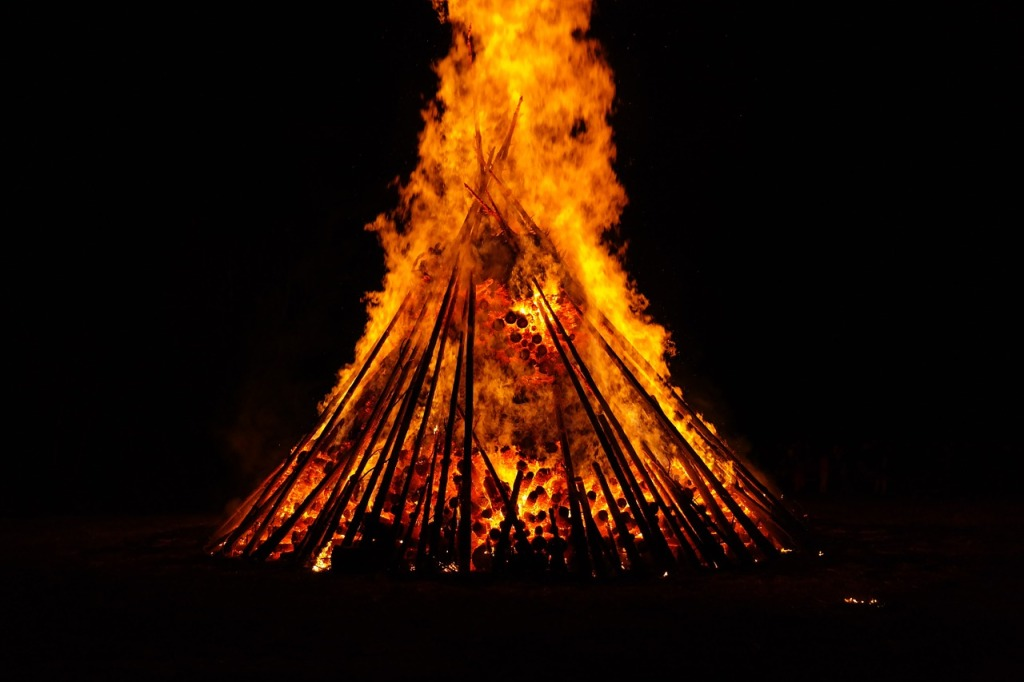 A large bonfire burns at night.